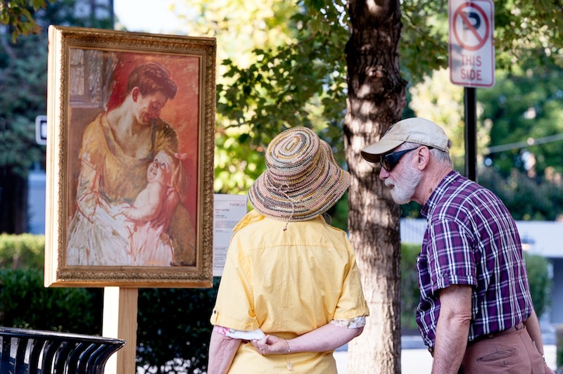 Passersby admire a serene Mary Cassatt painting in Louella Court.