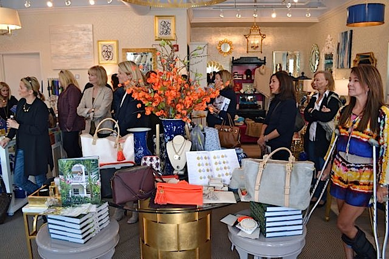 An invitation-only crowd listens as India Hicks describes her new lifestyle collection (displayed on the table in the foreground).