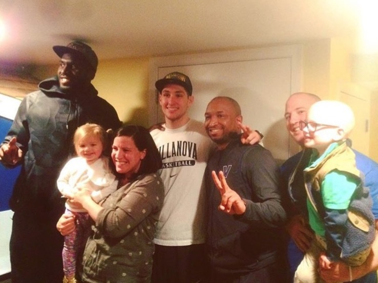 After the big surprise, Nova stars Daniel Ochefu and Ryan Archidiacono, Assistant Coach Ashley Howard pose with (from left) Lucy, 2, Annie, Andrew, and Blaise Davis, 4.