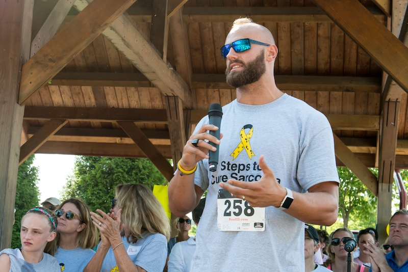 Pro football player Mark Herzlich addresses hundreds of fellow sarcoma survivors and their families at the second annual Steps for Sarcoma walk/run in Chesterbrook.