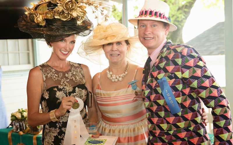 """. """"Best Head to Toe"""" winner Amy Holzapfel collects her ribbon with contest chair Laura Wood and Carson Kressley. Extra points for keeping a smile on her face while carrying a bottle of Dom Perignon on her head. (Brenda Carpenter photo)"""