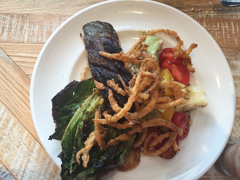A winning salad: grilled romaine, heirloom tomato, roasted corn, crispy onion salad with optional salmon.