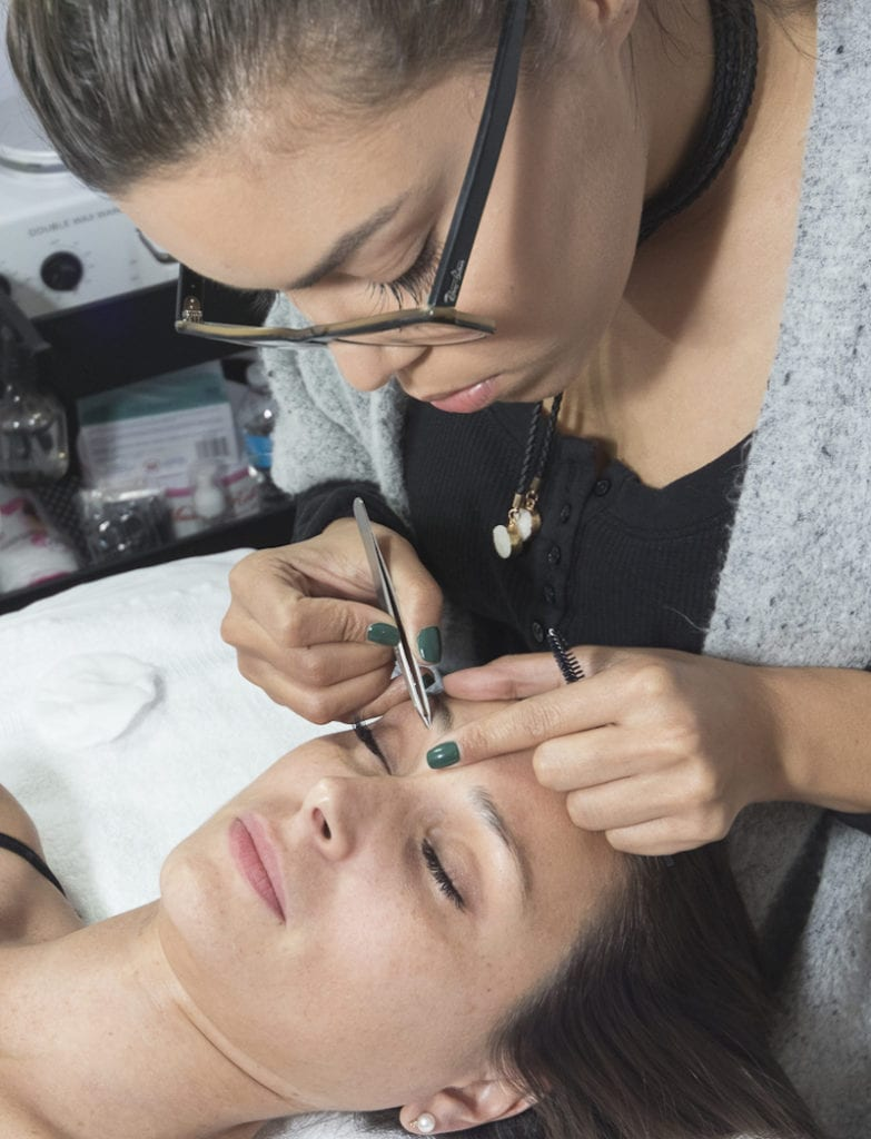 Marcel Dineen shapes a model's brows at her eponymous salon in Bryn Mawr.