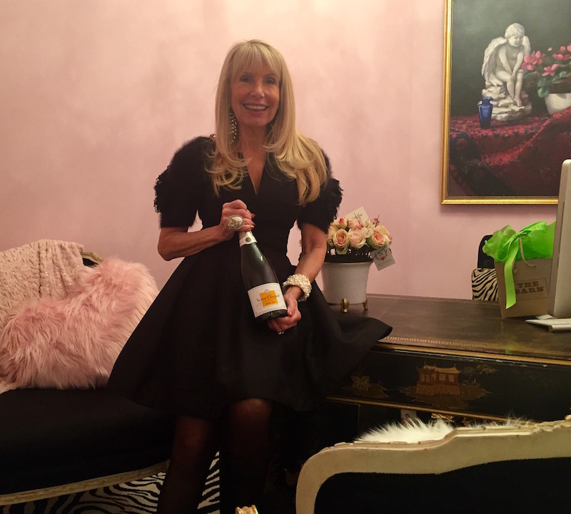 Deborah hoists a champagne bottle in her new office. She outfitted her new store with wares from local vendors like Malvern's Knots and Weaves, who supplied her office's zebra rug and the showroom's pink orientals.